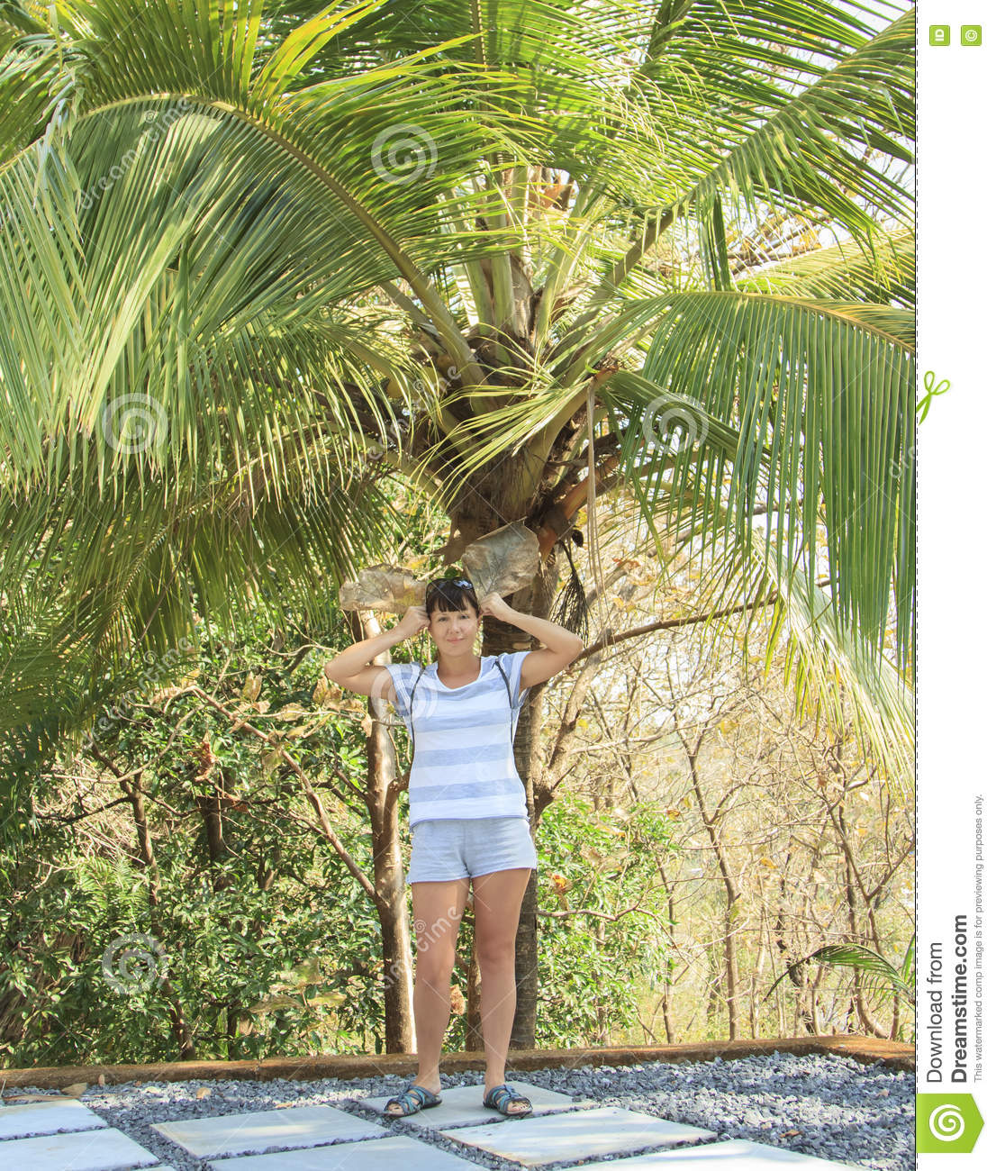 Portrait of beautiful young woman under a palm tree by
