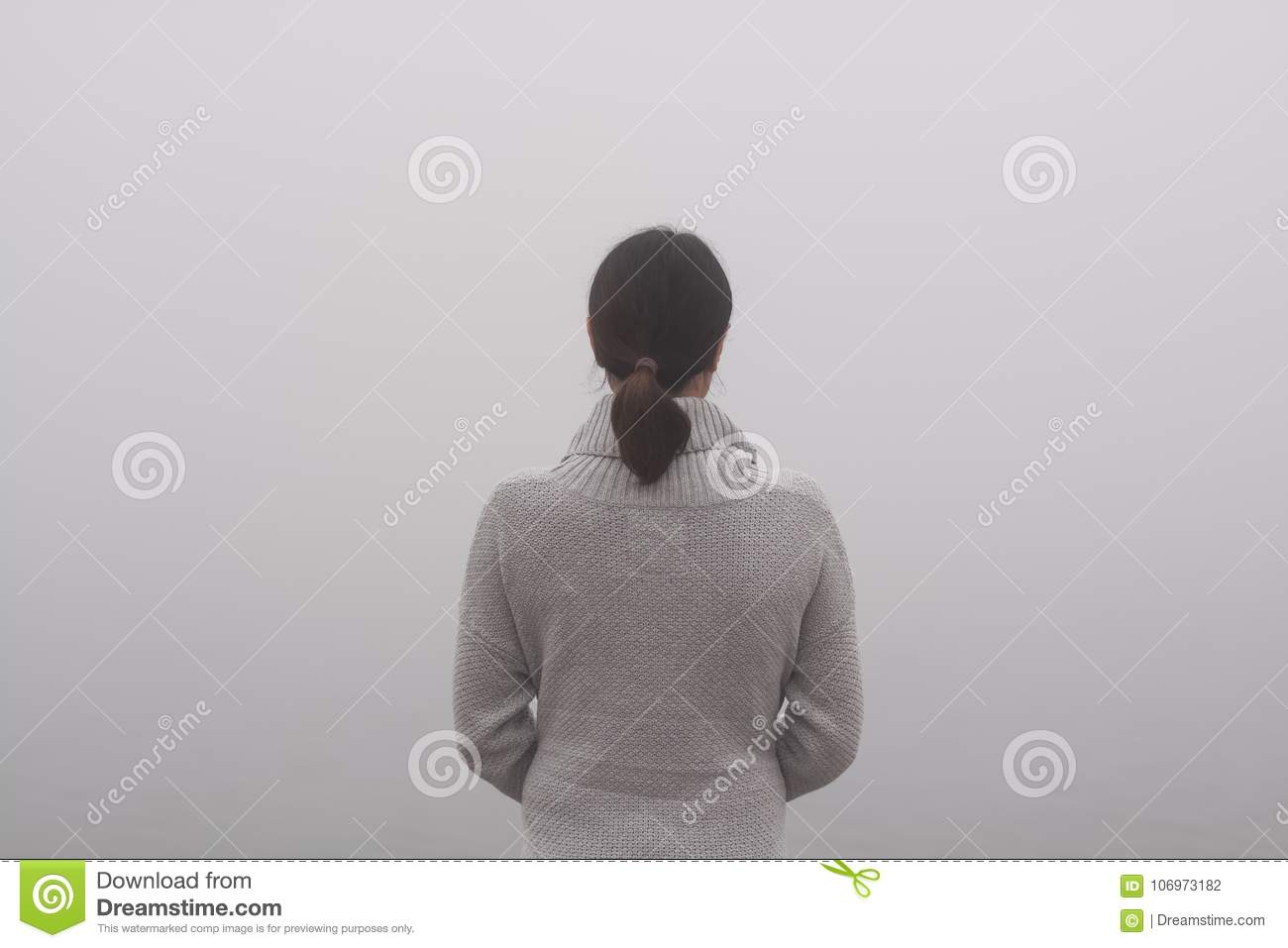 Young woman is standing by the water on a foggy day