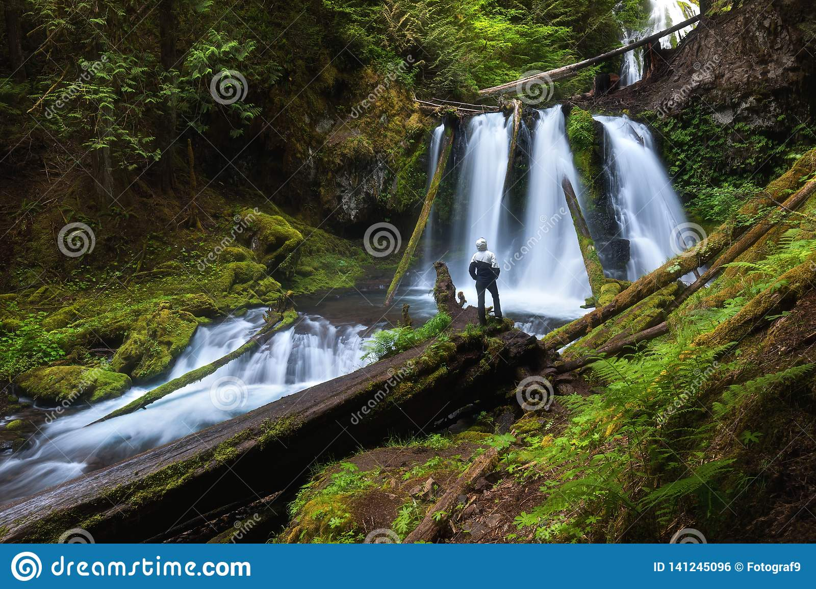 Young woman standing by a waterfall in Douglas County in the U.S. state of Oregon.[. The long exposure shots two degrees of water