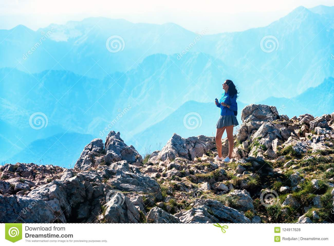 Young woman stands on the rocks.