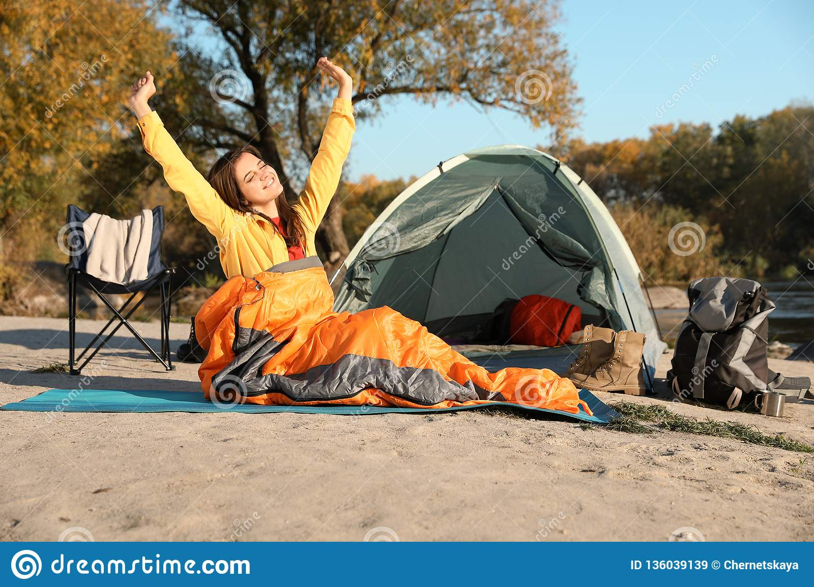 Young woman stretching in sleeping bag near camping tent