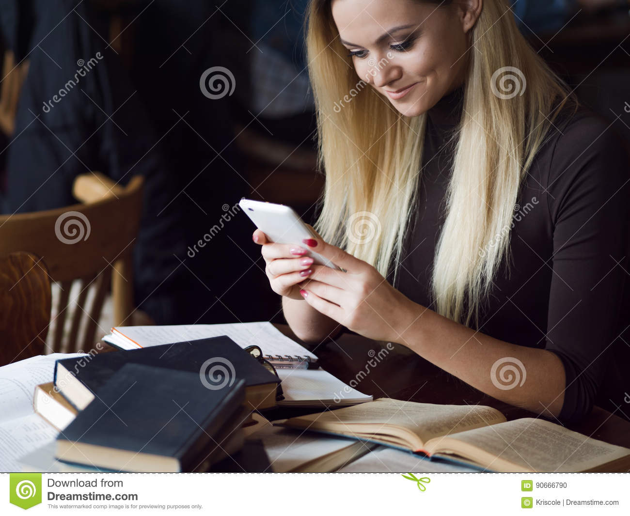 Young woman student of the University. Preparing exam and learning lessons in public library.