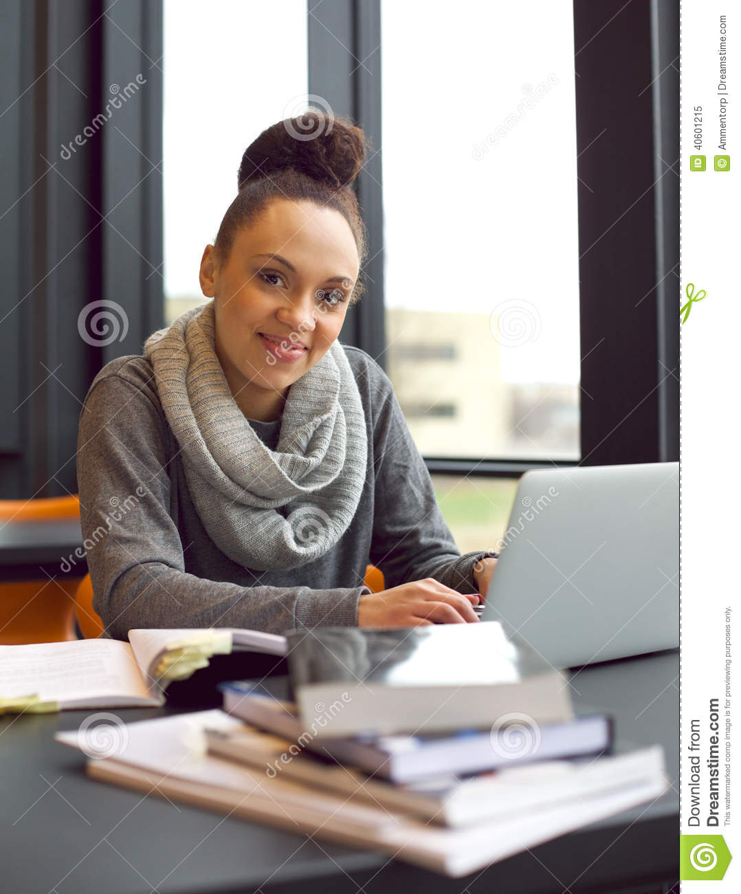 Young woman studying at a desk using books and laptop