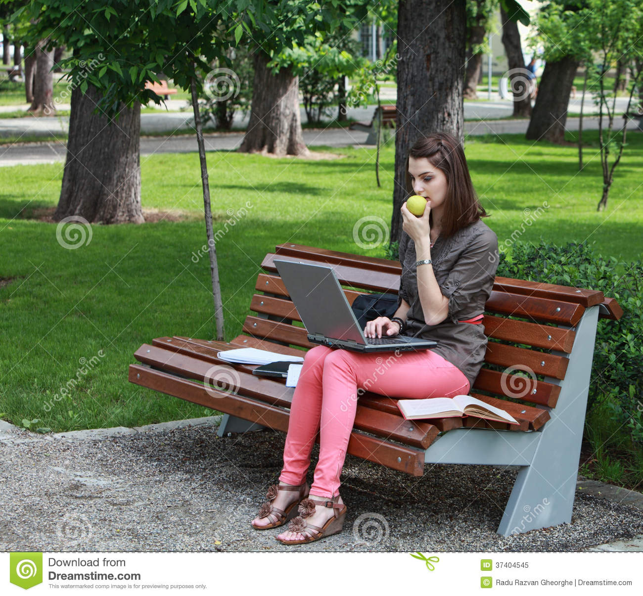 Young woman sitting on a bench in a park and working on a laptop while ...