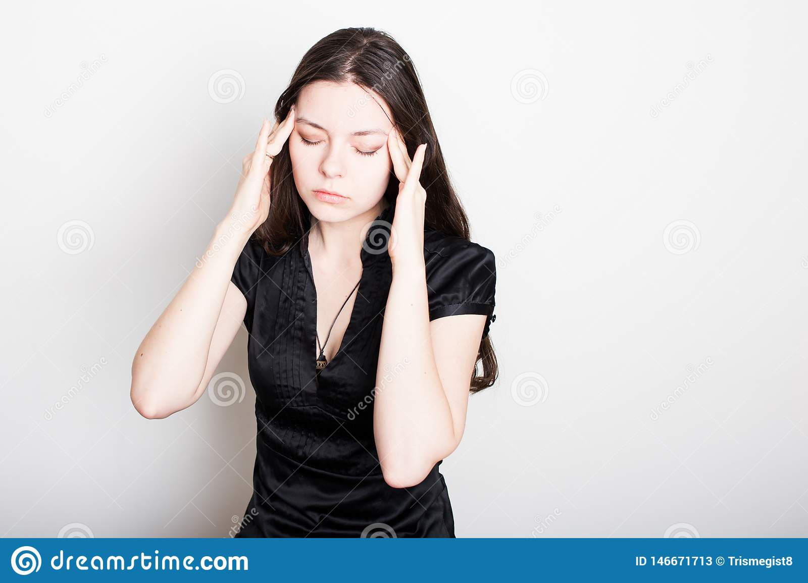 Young woman is suffering from a headache. Portrait of a girl clutching her head. Migraines and blood pressure problems