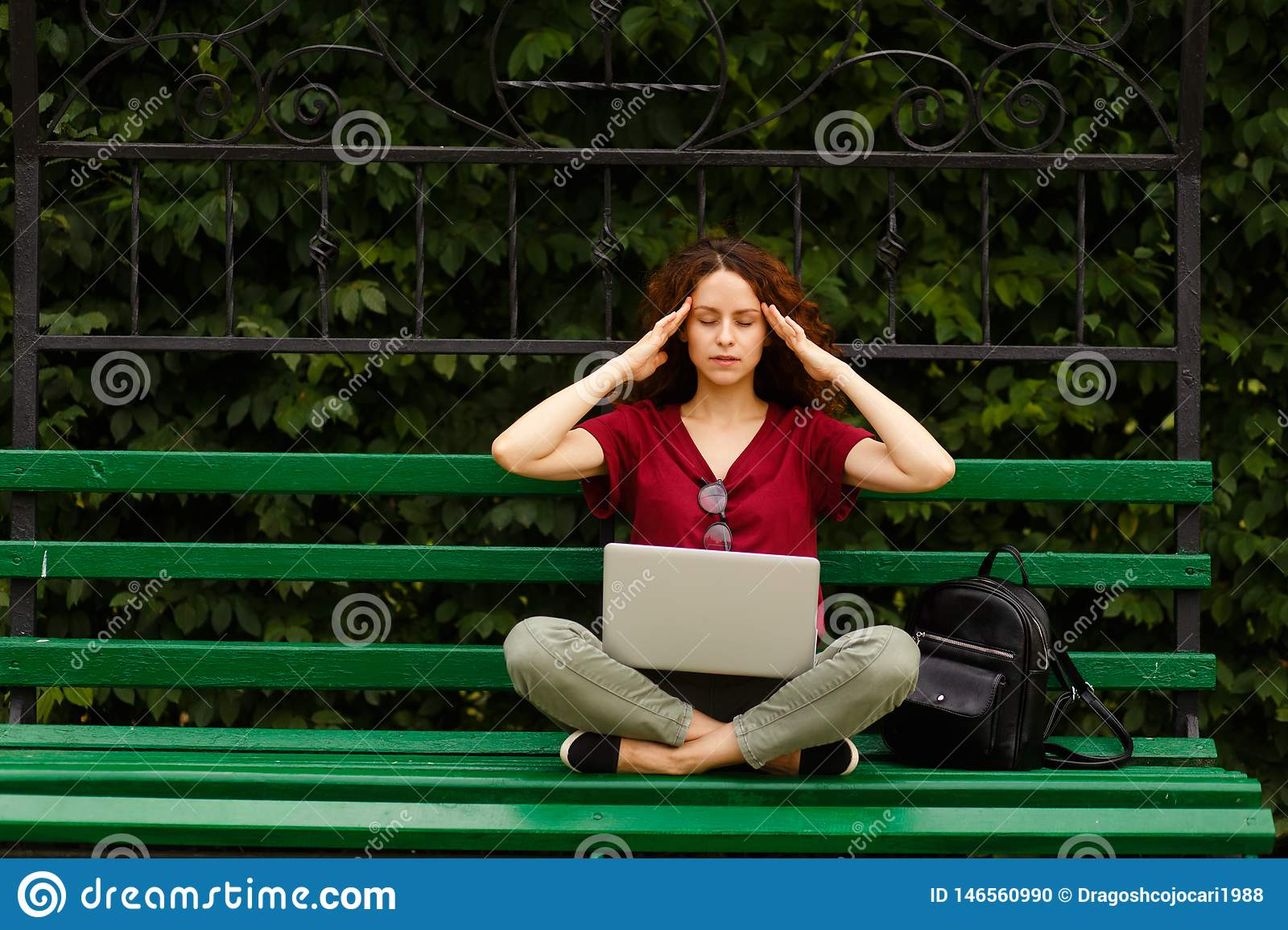 A curly young woman with closed eyes, working on a laptop, seated on a green bench in park touche her temples.