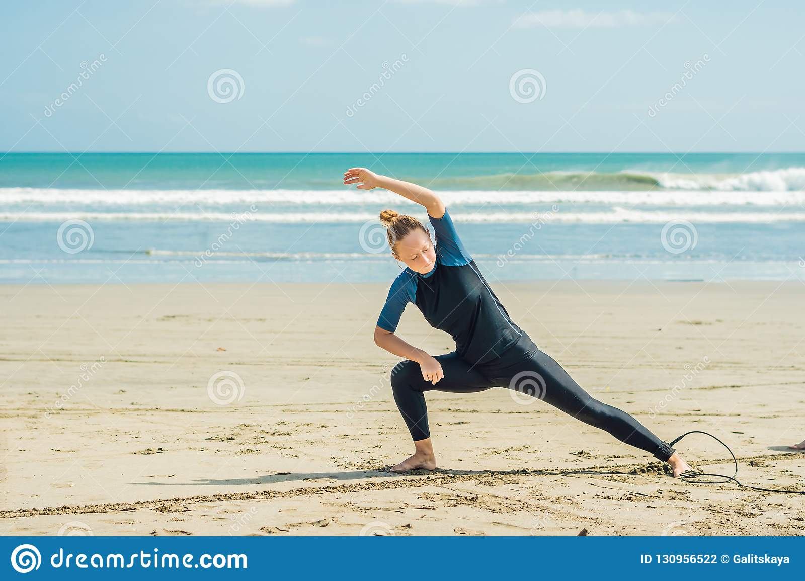 Young woman surfer warming up on the beach before surfing