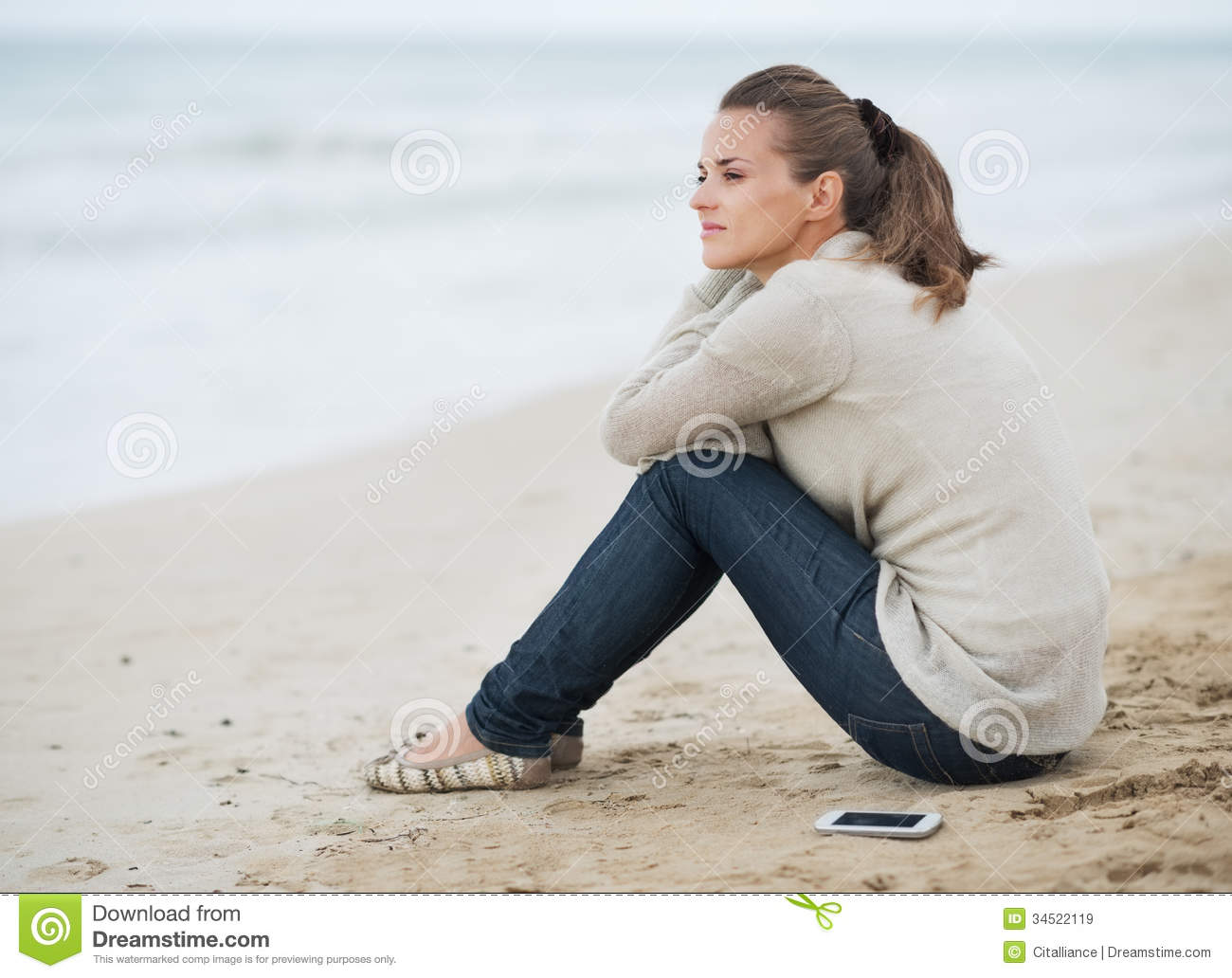 Young woman in sweater with cell phone sitting on lonely beach
