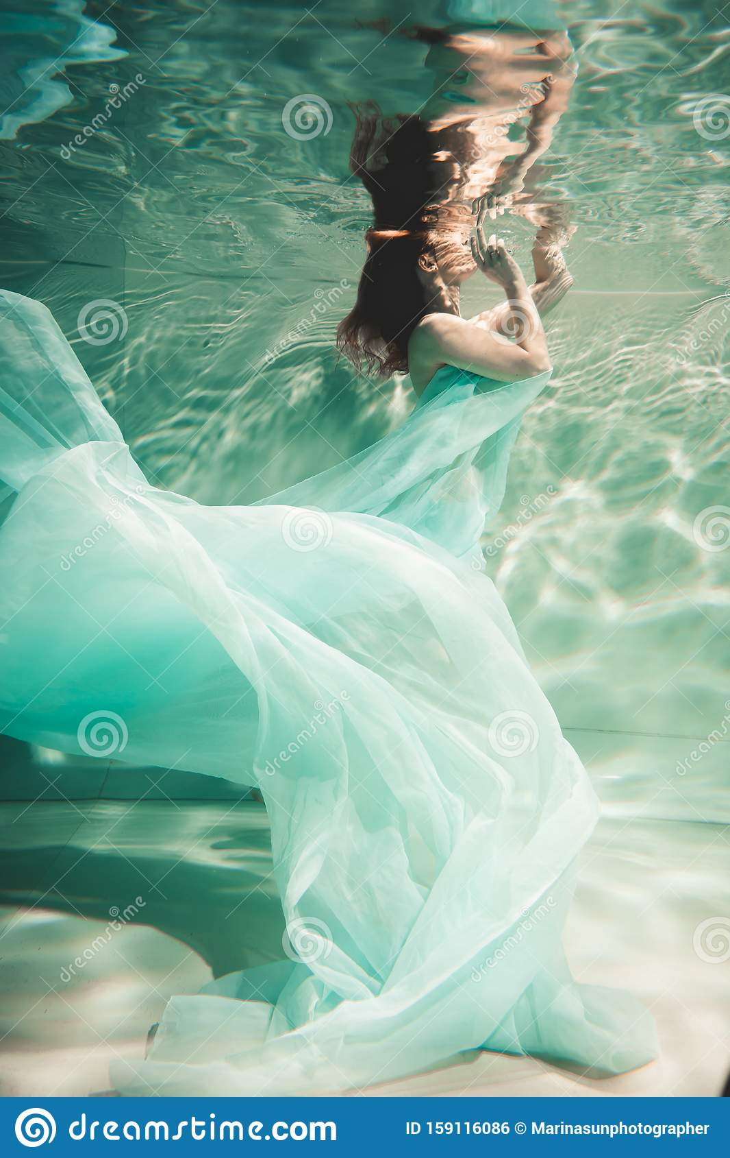 Young Woman Swimming Alone With Fashion Fabric Underwater