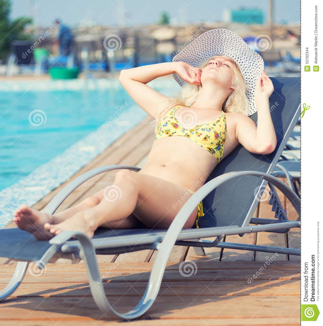Young woman in swimsuit laying on chaise-longue