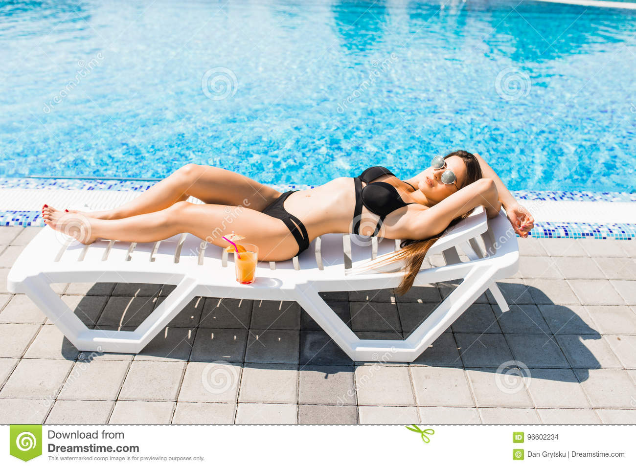 Young woman in swimsuit relaxing with cocktail on chaise longue. Summer time