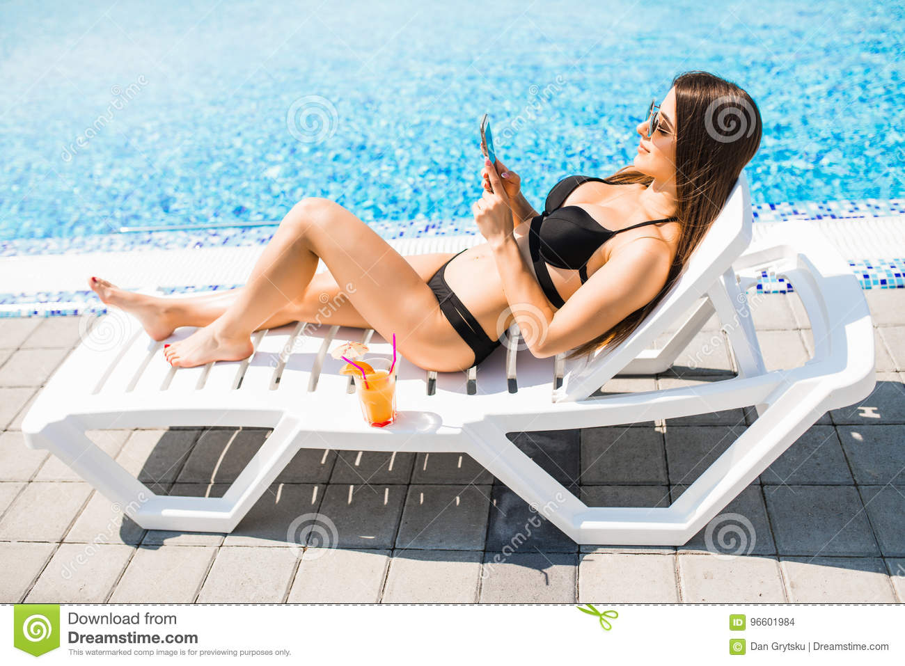 Young woman in swimsuit relaxing with cocktail on chaise longue and use her phone for texting. Summer time