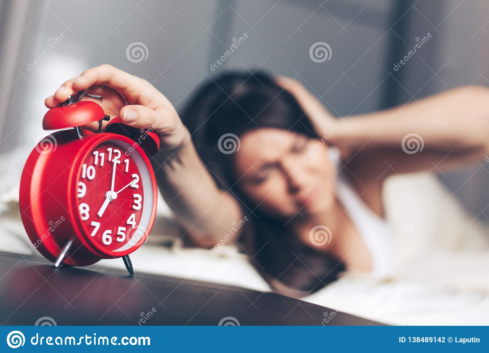 Young woman switches off the alarm clock on the bed in the morning