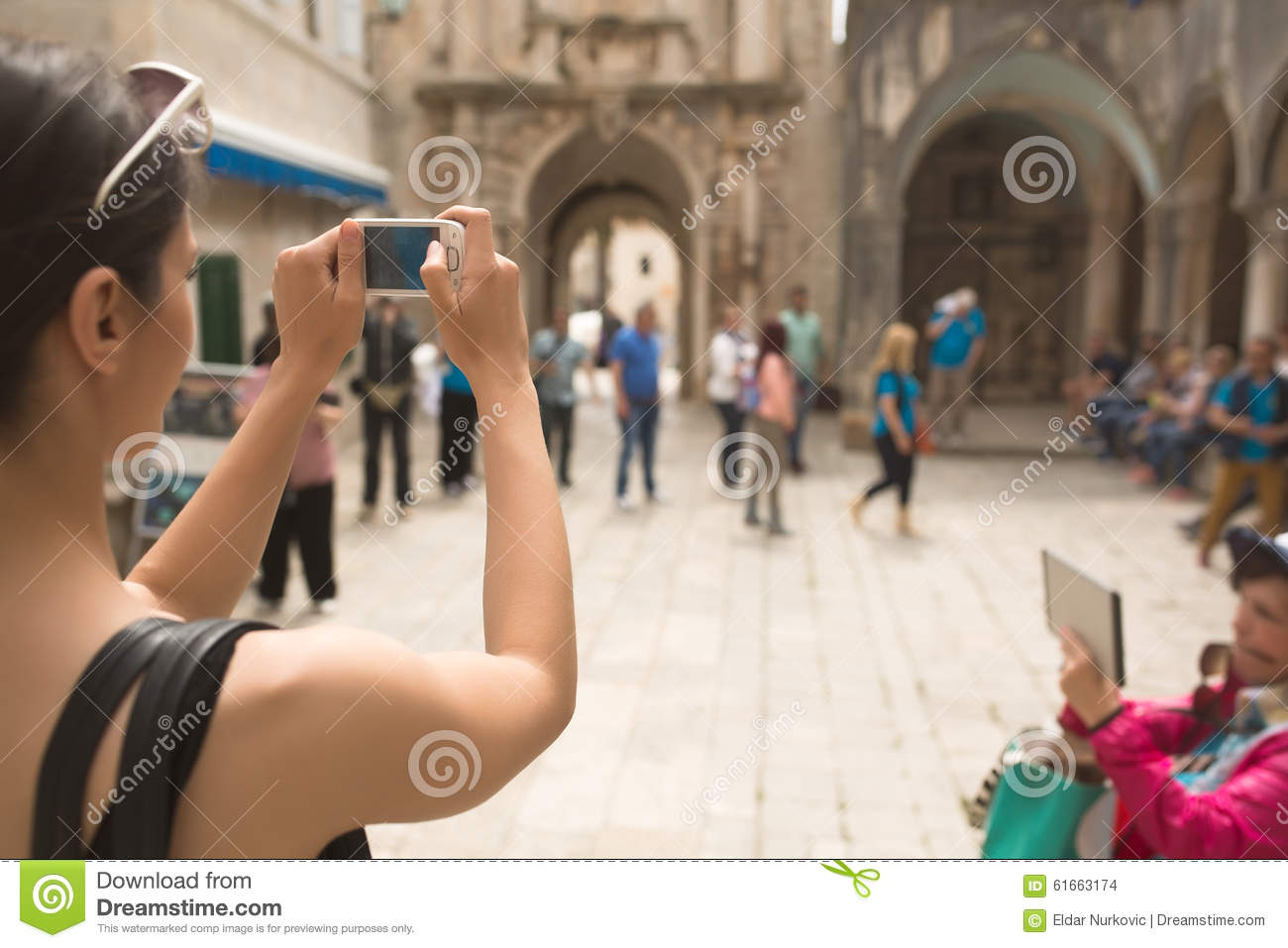 Young woman taking a photo with her smartphone. Woman tourist capturing memories. Tourist tour around city. Young woman tour