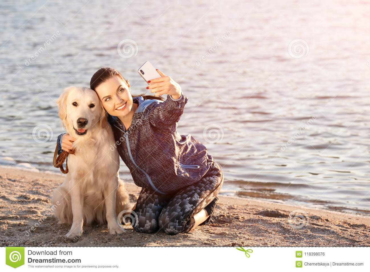 Young woman taking selfie with dog on beach. Pet care
