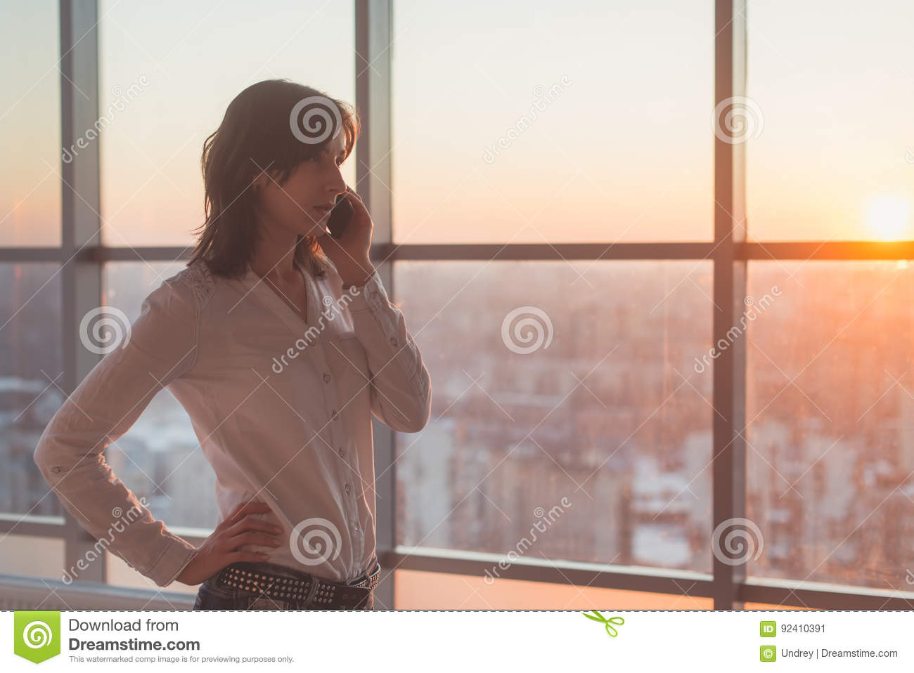 Young woman talking using cell phone at office in the evening. Female businesswoman concentrated, looking forward