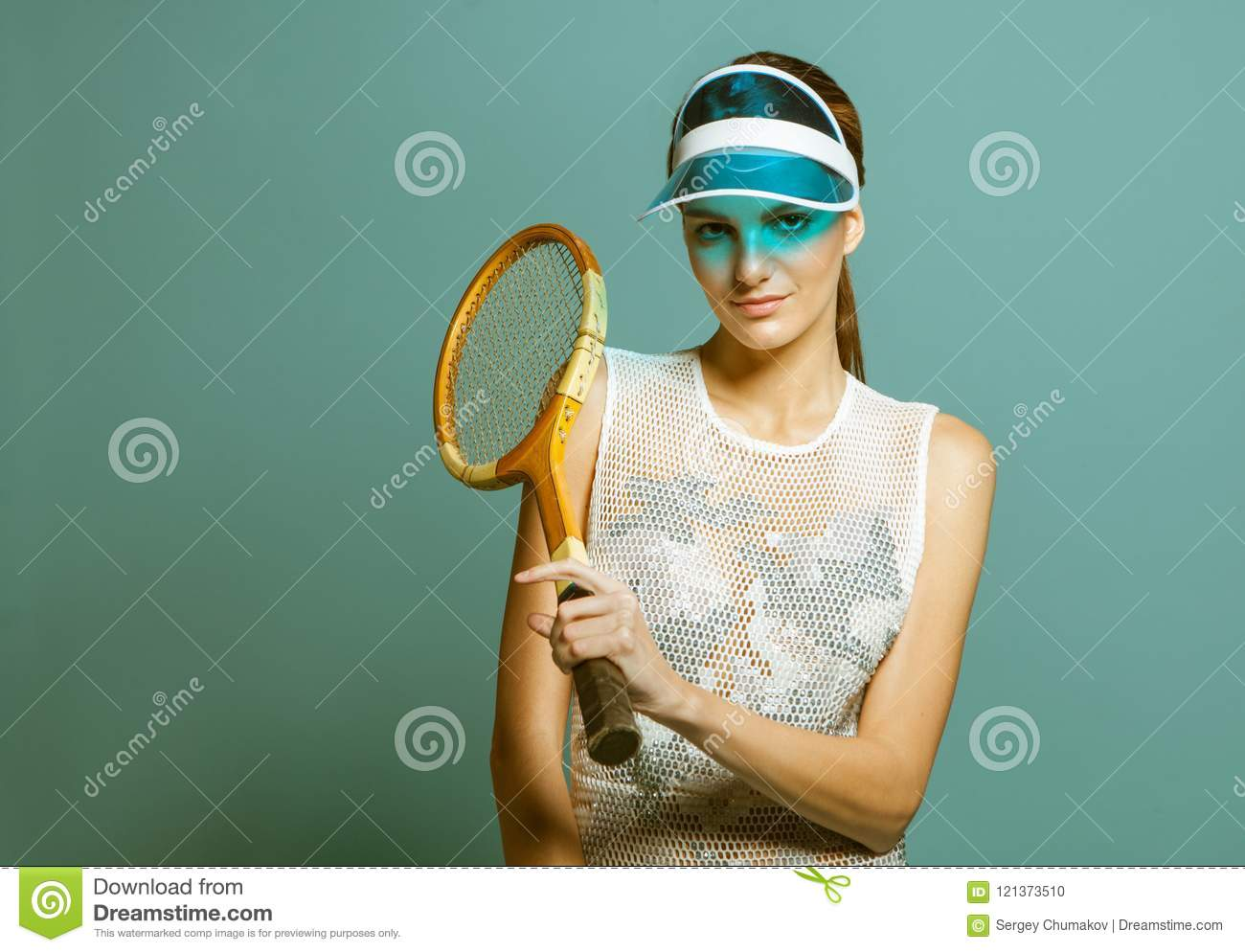 Young female tennis player in sun visor holding tennis racquet on blue  studio background 0143414bf3f