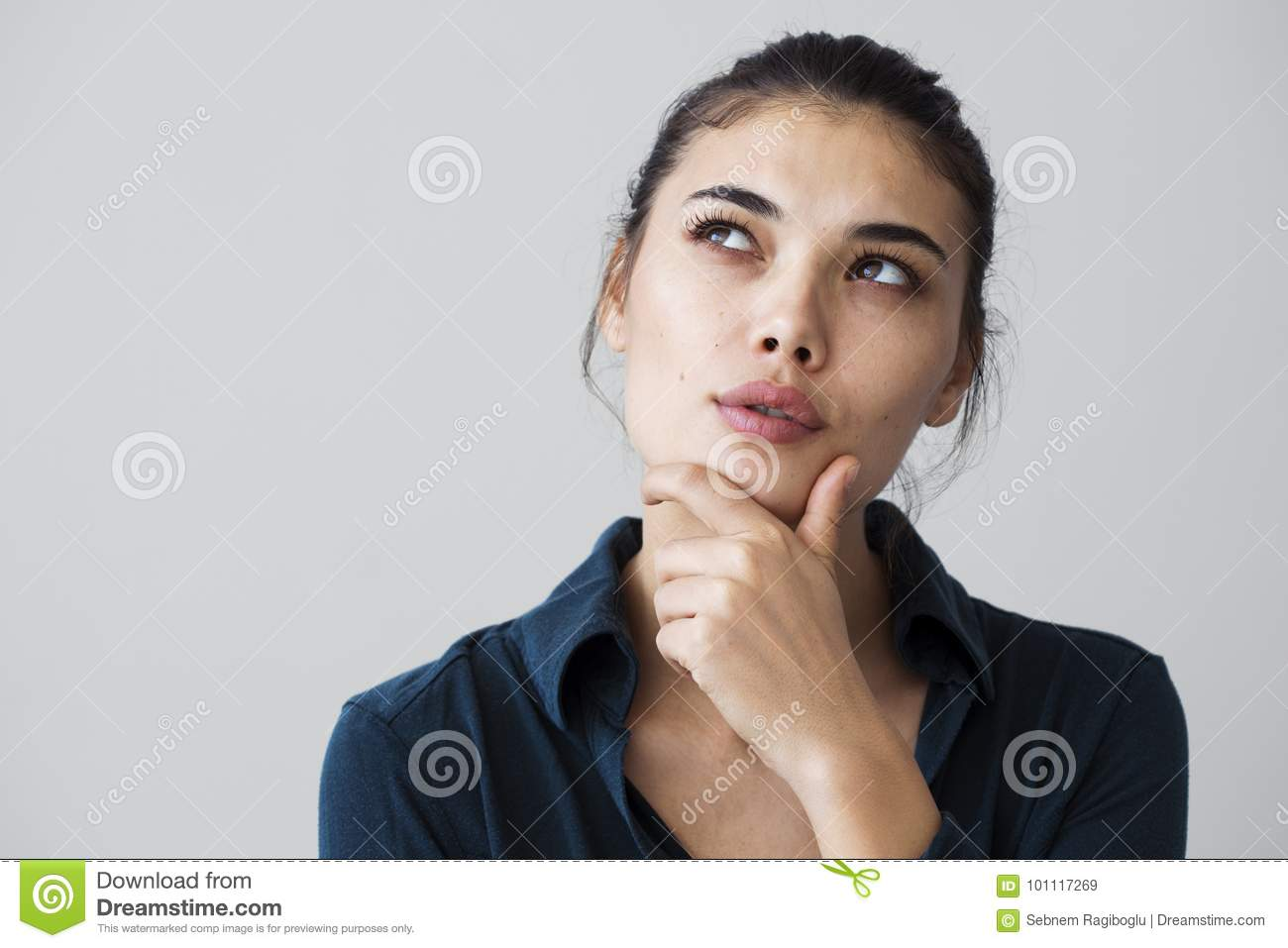 Young woman thinking on gray background