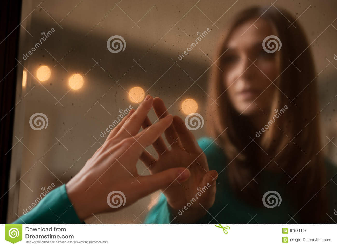 Young woman touching her own reflection in a mirror