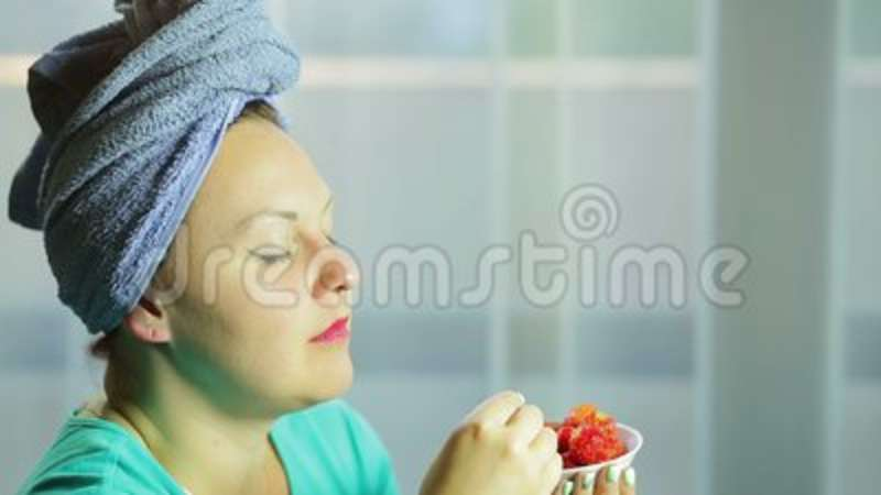 A Young Woman With A Towel On Her Head Puts The Strawberry In Her