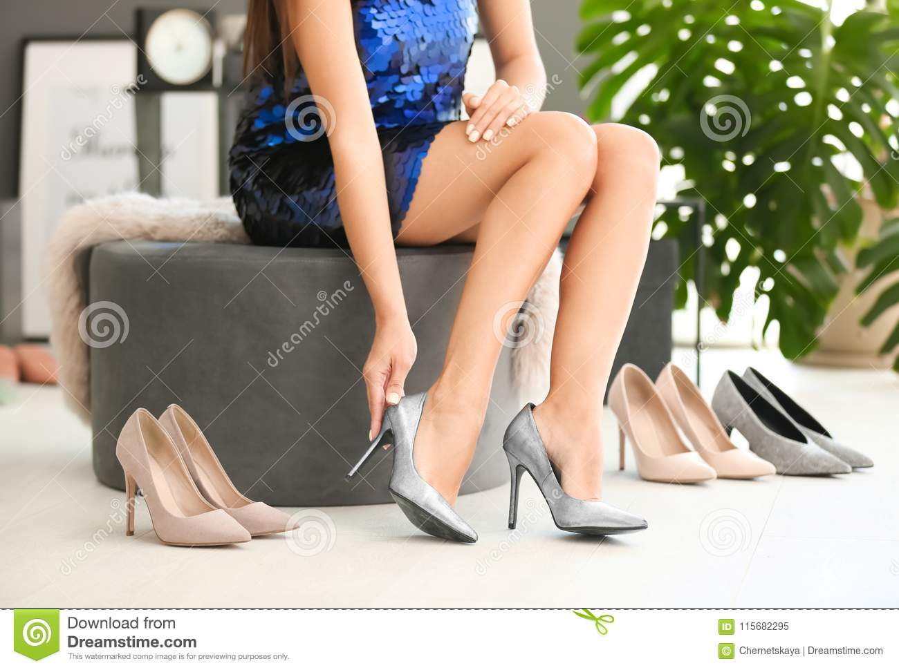 Young woman trying on high-heeled shoes
