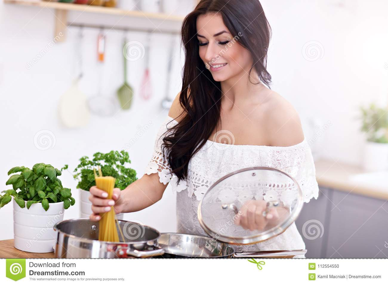 Young woman trying to prepare pasta in kitchen