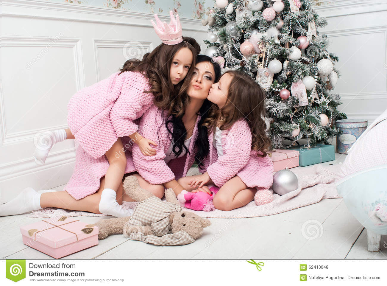 Young Woman With Two Girls Near The Christmas Tree Among The Gifts