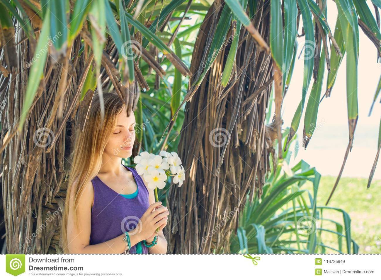 Young Beautiful Woman Relaxing Under The Palm Tree On A