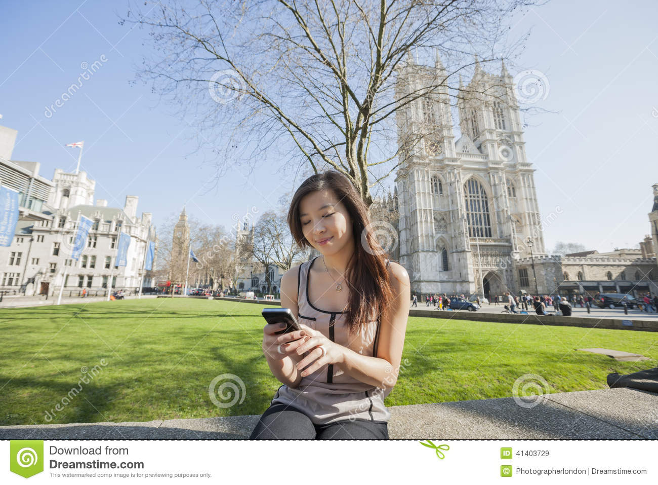 Young Woman Using Cell Phone Against Westminster Abbey In