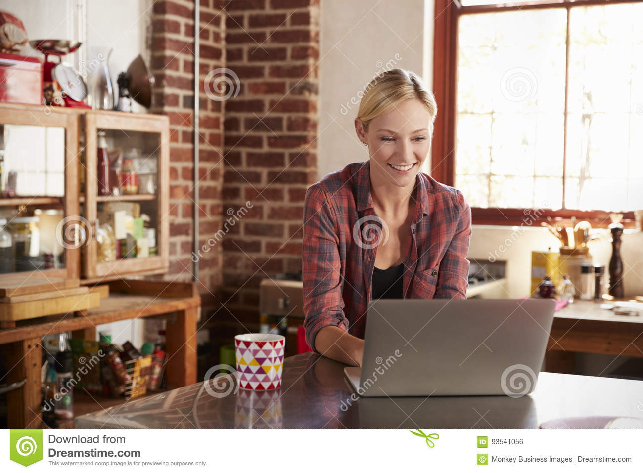 Young woman using computer in kitchen, close up front view