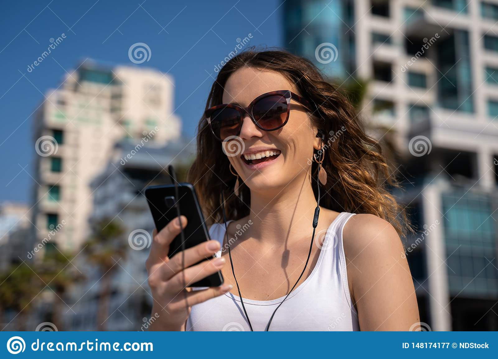 Young Woman Using The Phone With Headset City Skyline In Background Stock Image Image Of Enjoying Cell 148174177