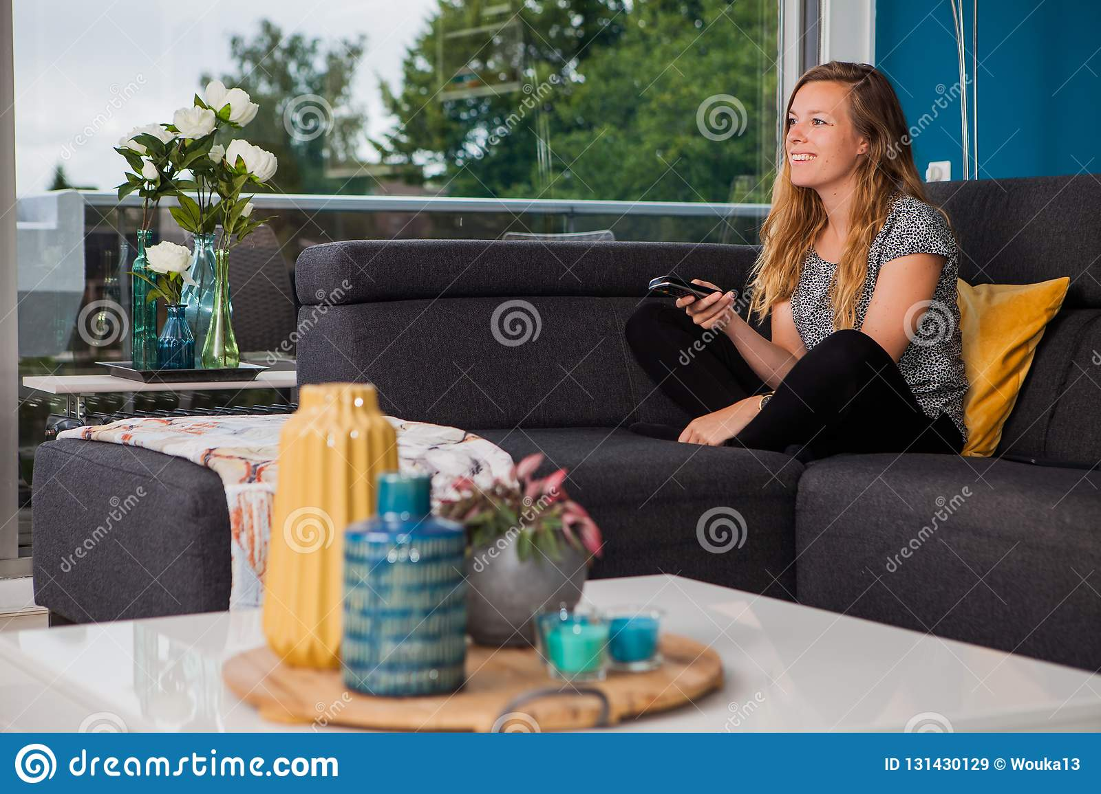 Young woman using a remote control on the couch