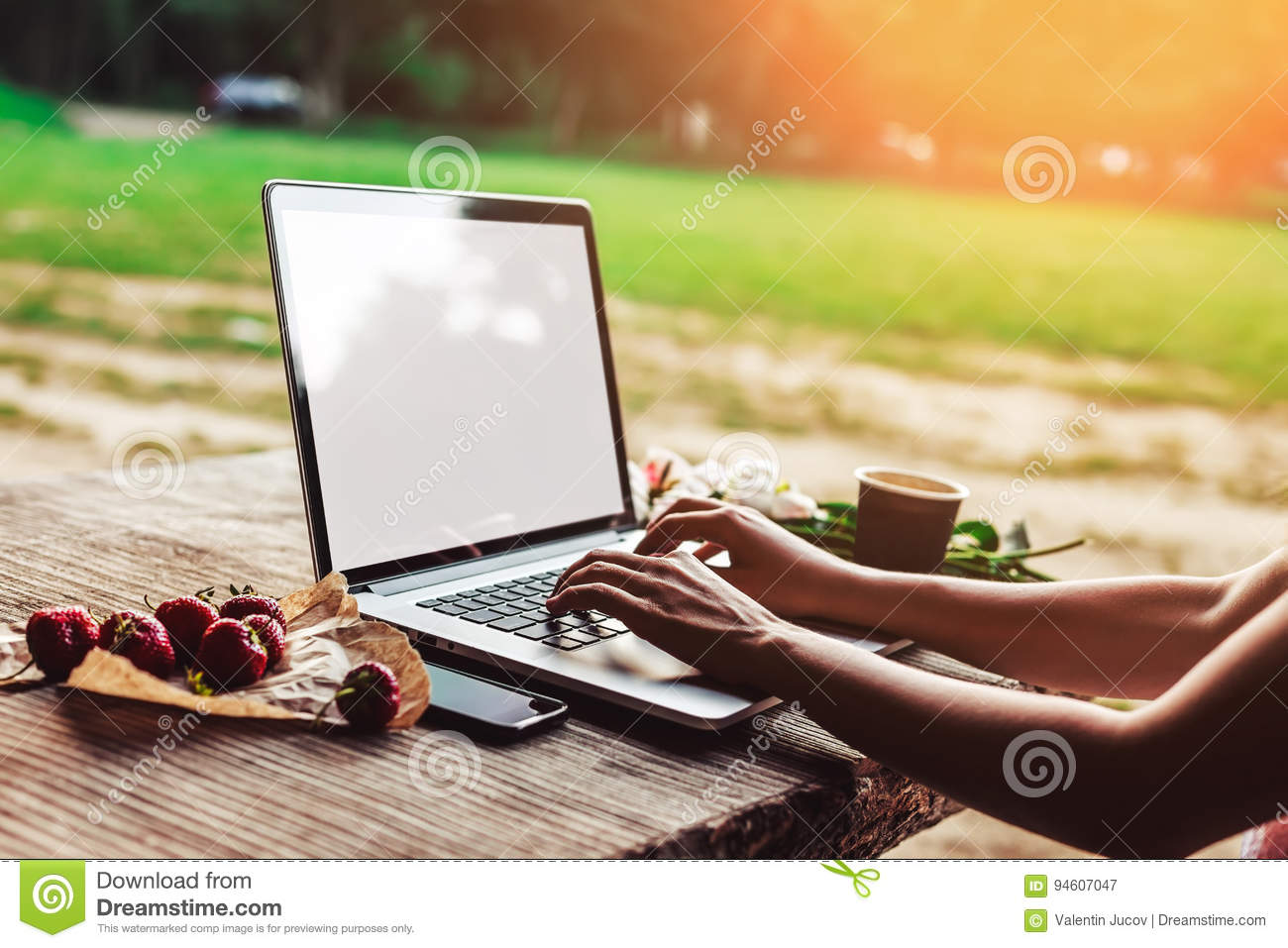 Young woman using and typing laptop computer at rough wooden table with coffee cup, strawberries, bouquet of peonies flowers,