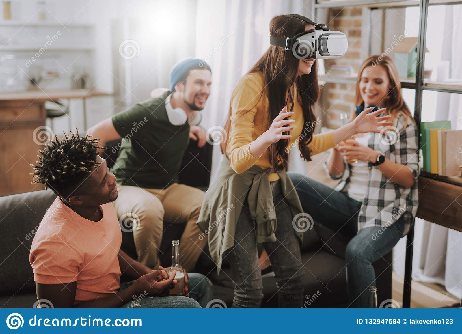 Young woman using VR headset while spending time with friends