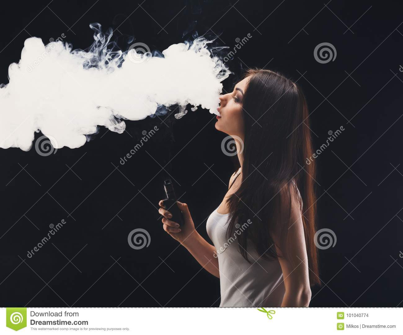 Young woman vaping e-cigarette with smoke on black