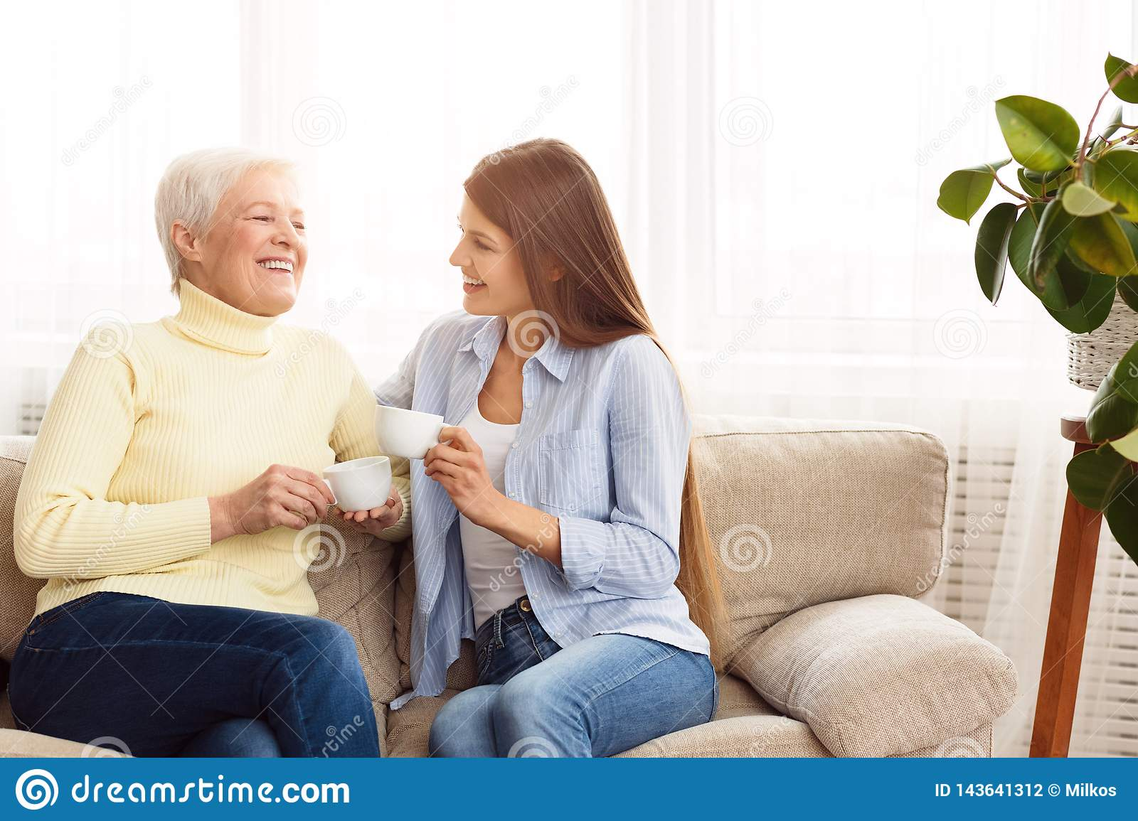 Young woman visiting senior mother and drinking coffee together