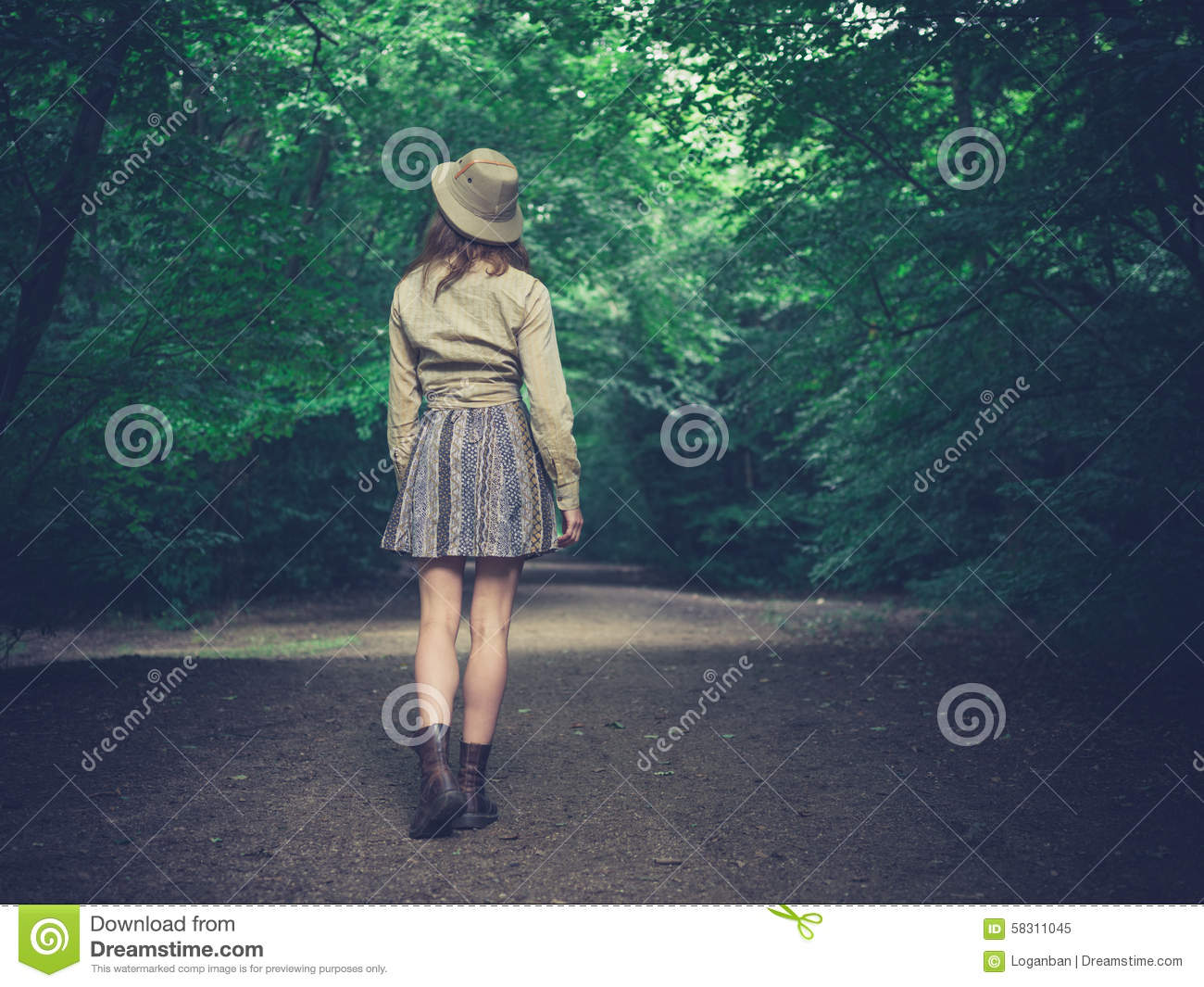 Woman Walking Down Dirt Road In Forest High-Res Stock