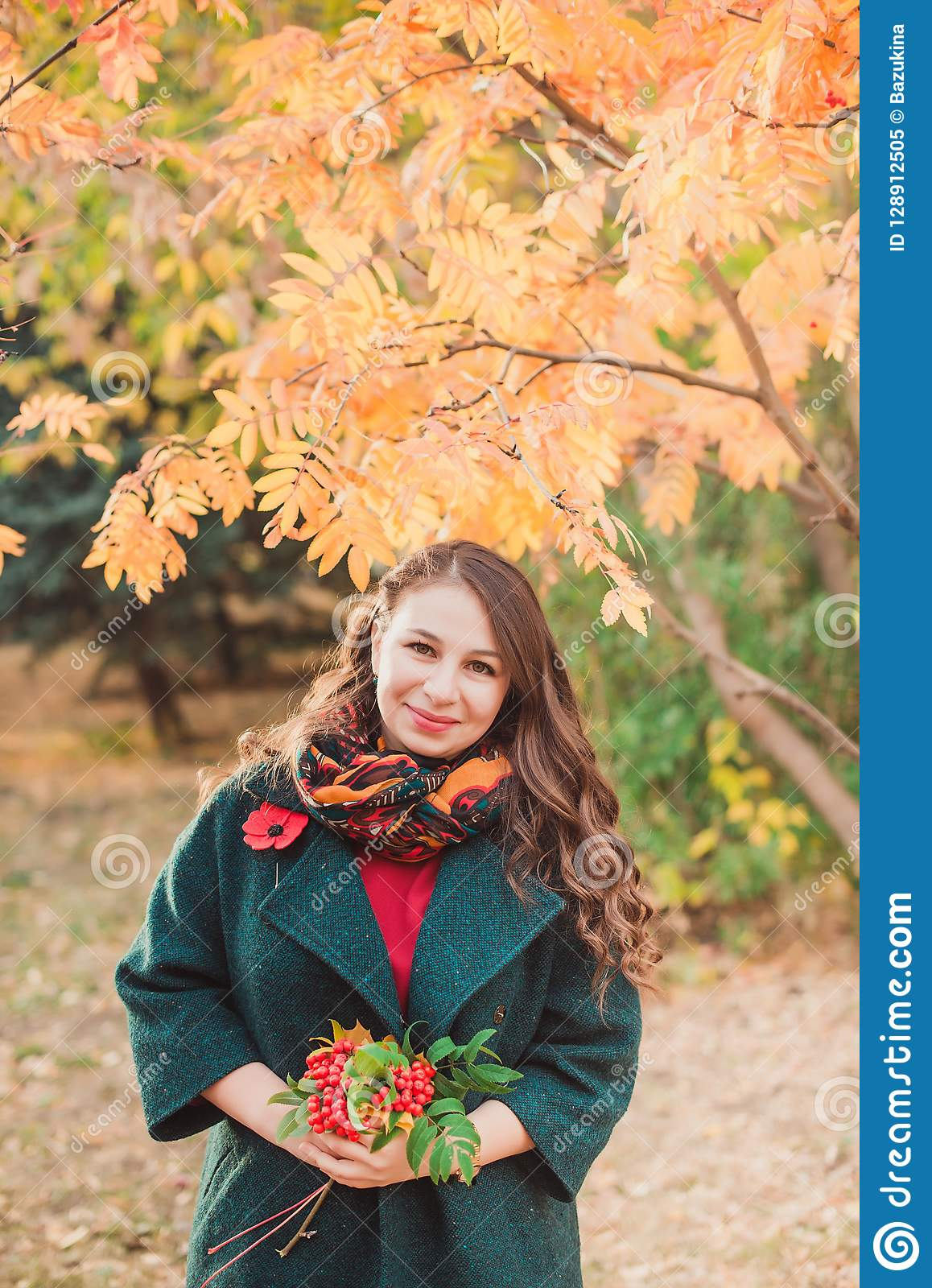 A young woman walks in the autumn Park. Brunette woman wearing a green coat. She is holding a bouquet of yellow leaves