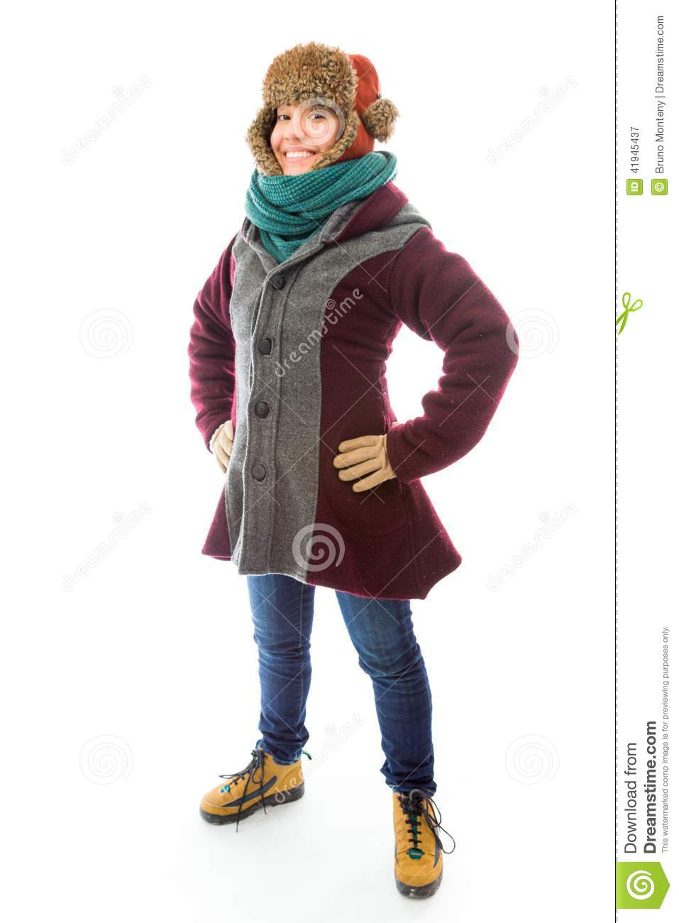 Young woman in warm clothing and standing with her arms akimbo
