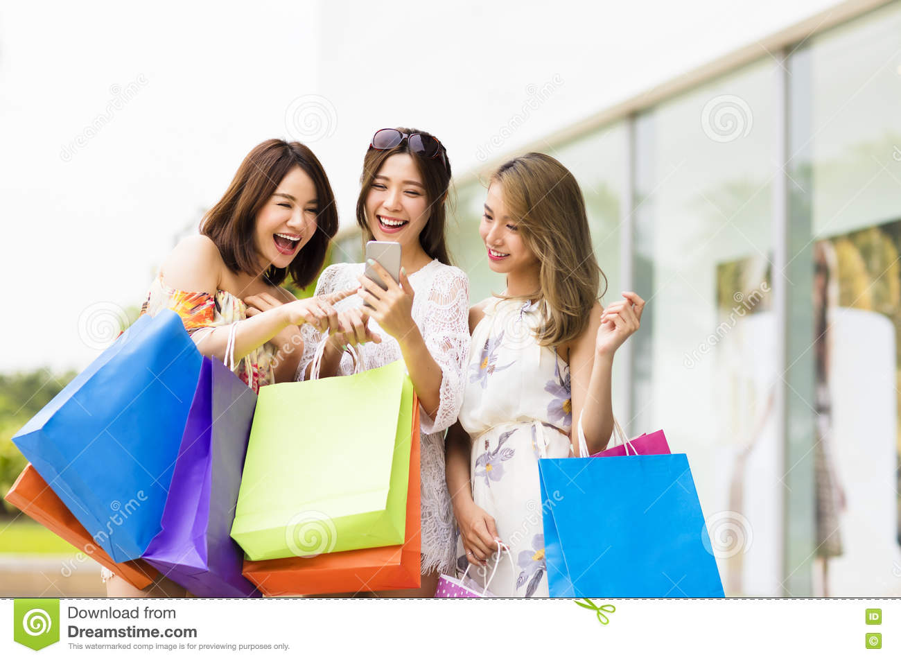 young woman watching smart phone in shopping mall