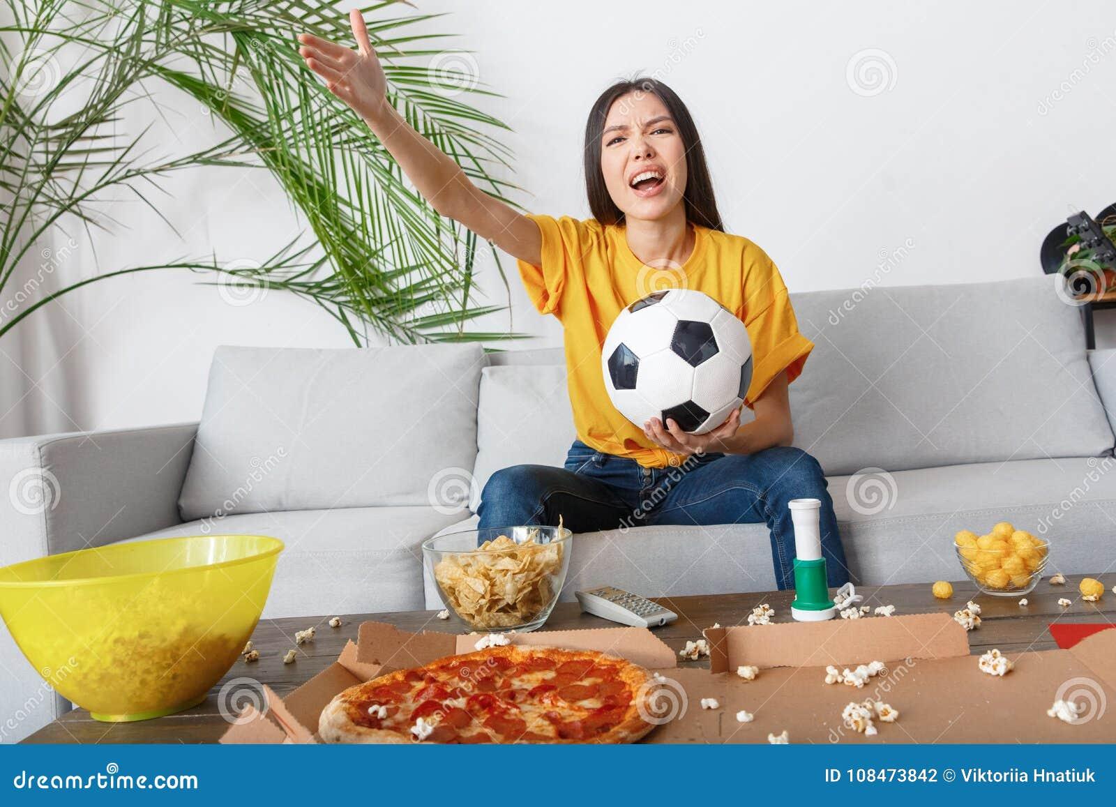 Young woman sport fan watching match in a yellow t-shirt shouting angry