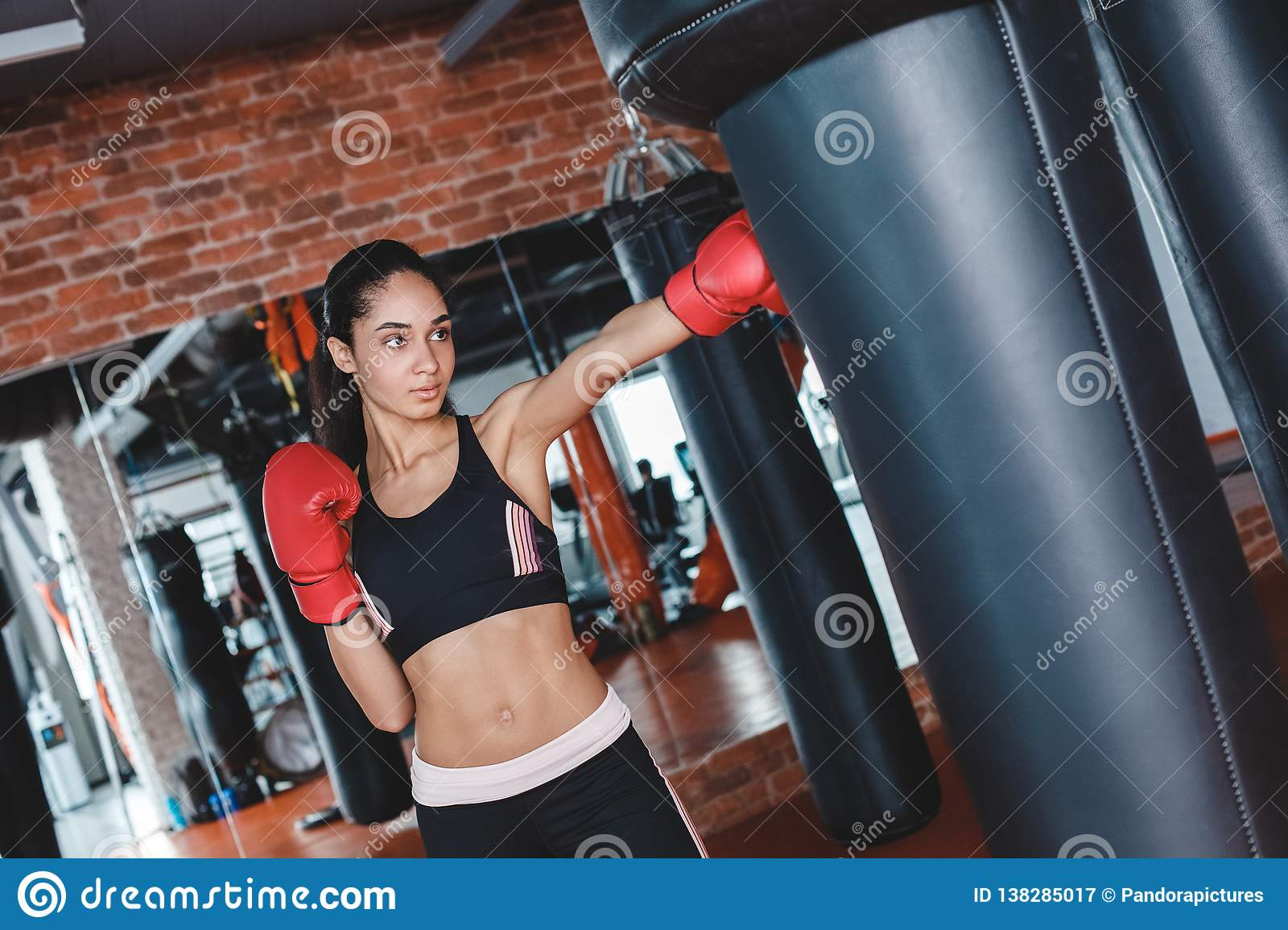 Young woman in boxing gloves in gym standing kicking punching bag concentrated