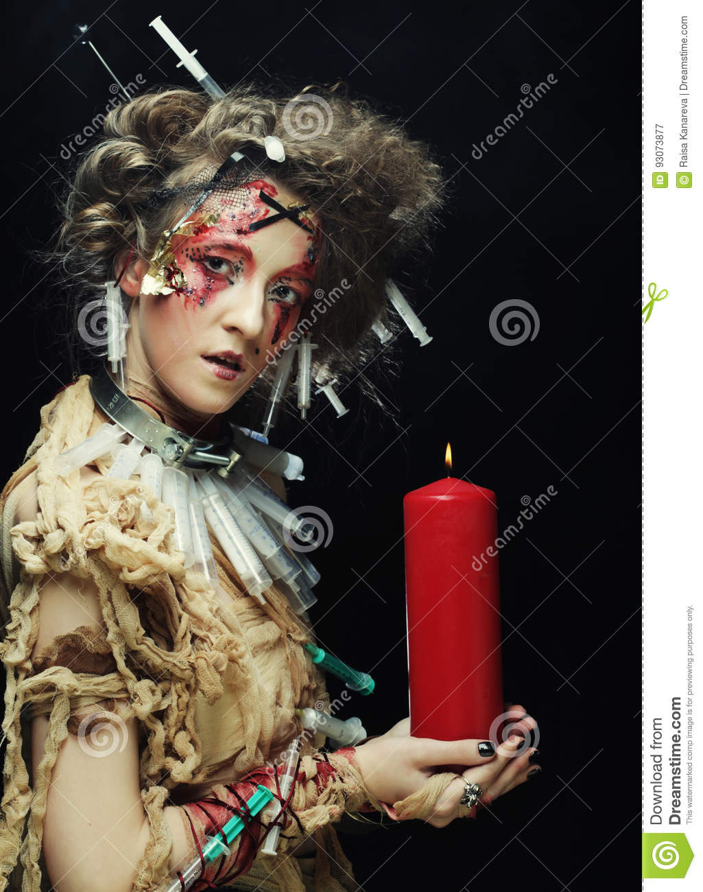 Young woman wearing carnival costume holding a candle.