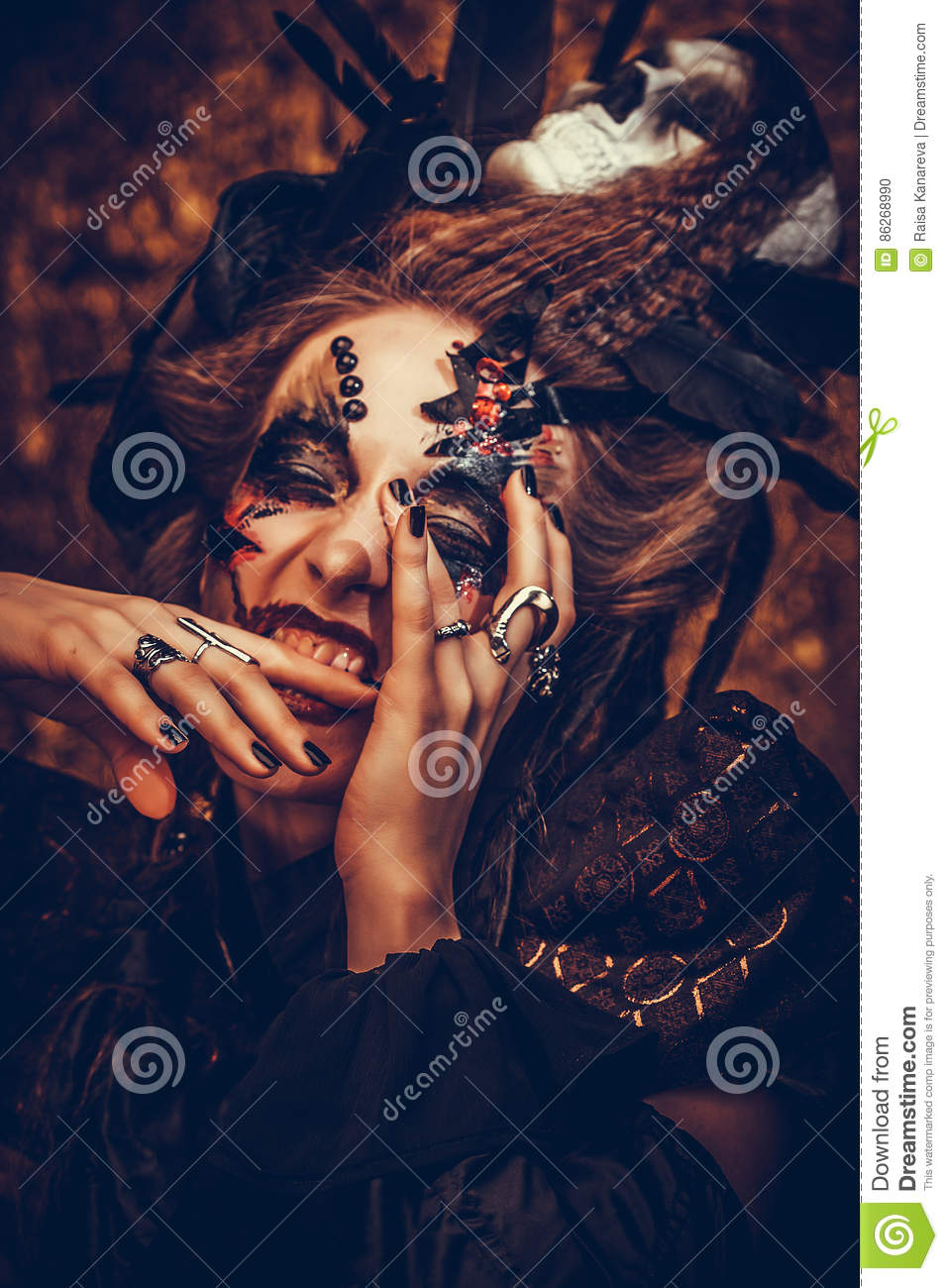 Young woman wearing dark costume. Bright make up and smoke- halloween theme.
