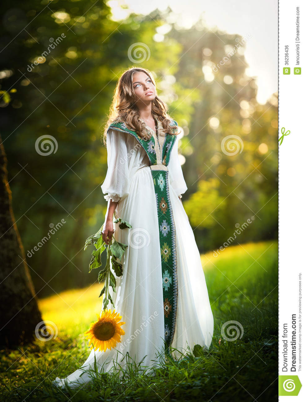 Young Woman Wearing A Long White Dress Holding A Sunflower ...