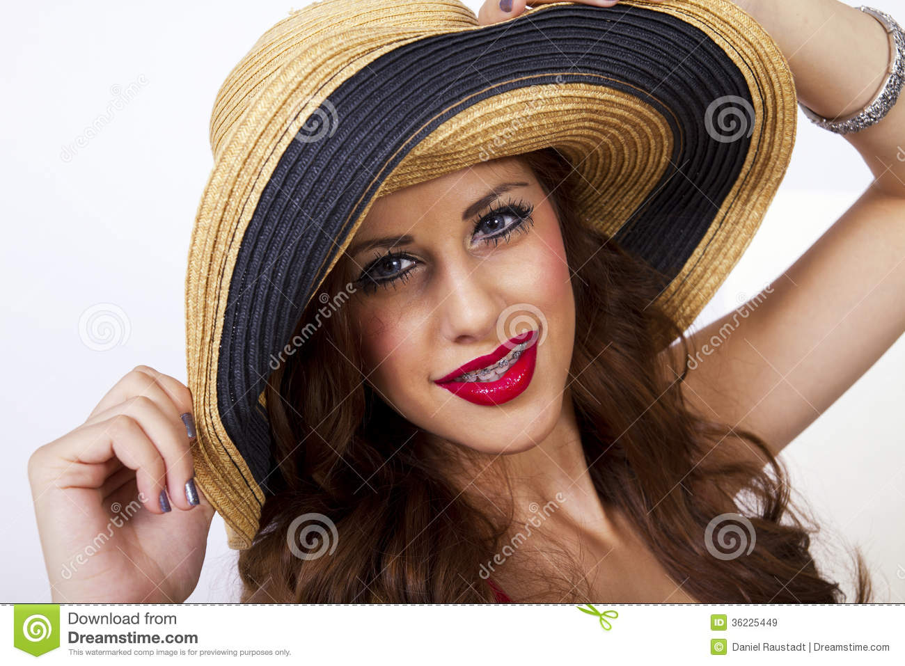 ... young woman wearing straw summer sun hat. She has braces on her teeth