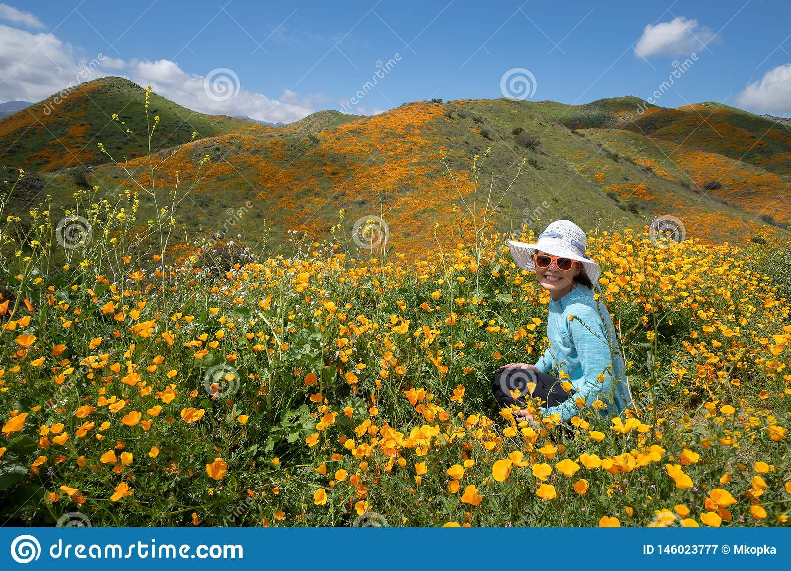Young woman wearing sunglasses and straw hat poses in poppy field in California