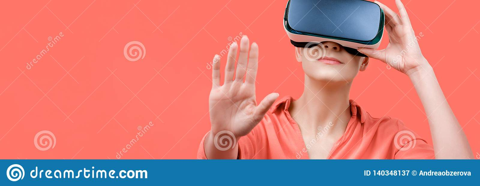 Young woman wearing virtual reality goggles. Woman wearing VR glasses over coral background. VR experience banner.