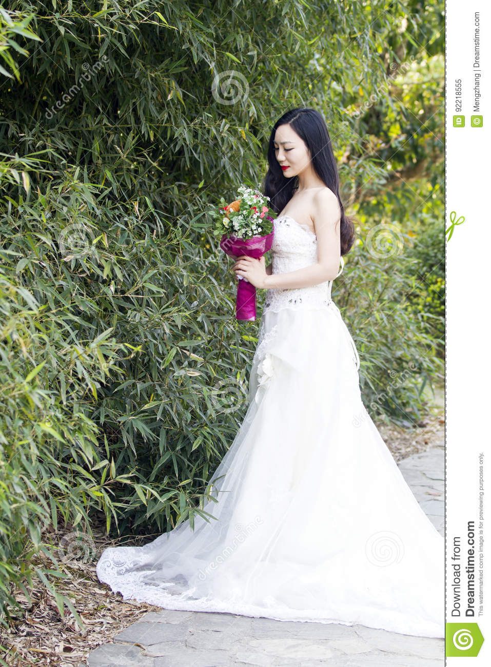 A young woman wedding photo/portrait stand by bamboos