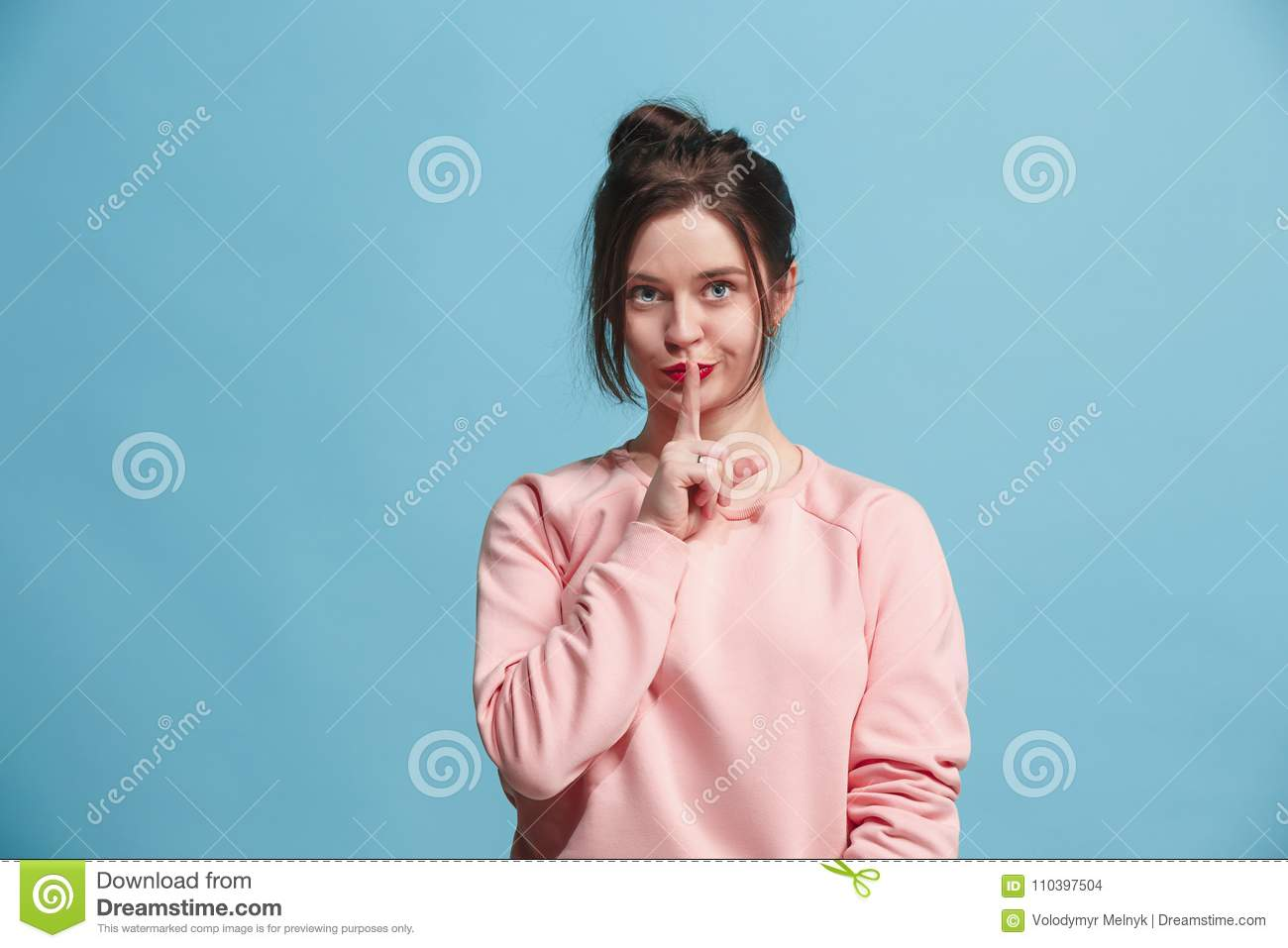 The young woman whispering a secret behind her hand over blue background